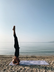 Young blond girl practice yoga headstand asana on sea shore at sunrise.