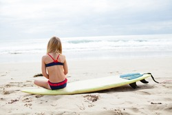Young blond girl sitting on surfboard on the beach looking towards ocean