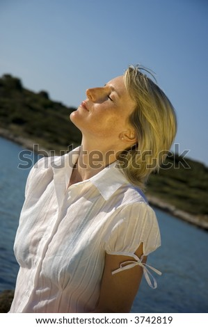 young blond girl sun bathing beside the sea