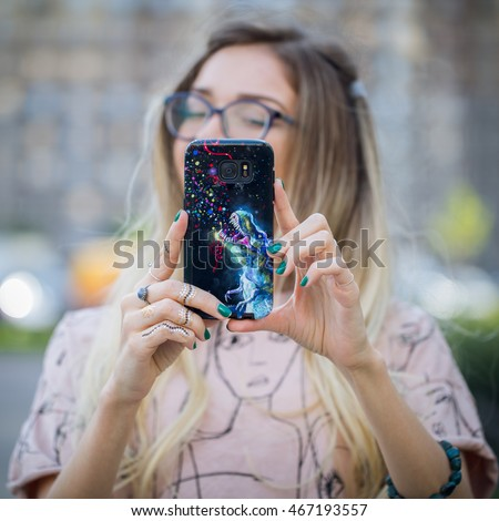 Young blond  girl taking a selfie with a phone. Custom artwork print on case. Blurred background.