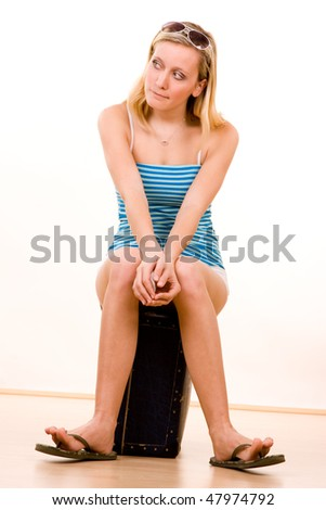 Young blond haired female holidaymaker with sunglasses sat on suitcase, white background.
