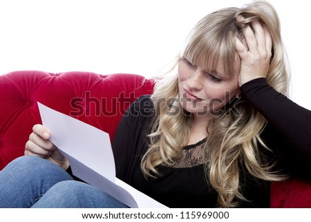 young blond haired girl on red sofa got bad news in front of white background