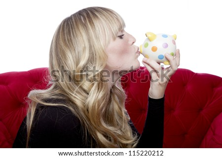 young blond haired girl on red sofa kisses piggy bank in front of white background