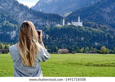 Young blond haired girl standing backwards on a green field, holding a photo camera and taking pictures from far away of the Neuschwanstein castle in Bavaria.