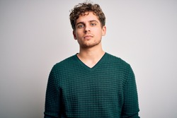 Young blond handsome man with curly hair wearing green sweater over white background Relaxed with serious expression on face. Simple and natural looking at the camera.