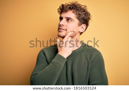 Young blond handsome man with curly hair wearing green sweater over yellow background with hand on chin thinking about question, pensive expression. Smiling with thoughtful face. Doubt concept.