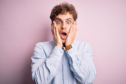 Young blond handsome man with curly hair wearing striped shirt over white background afraid and shocked, surprise and amazed expression with hands on face