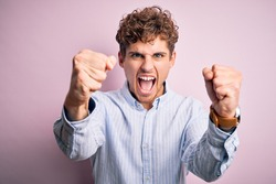 Young blond handsome man with curly hair wearing striped shirt over white background angry and mad raising fists frustrated and furious while shouting with anger. Rage and aggressive concept.