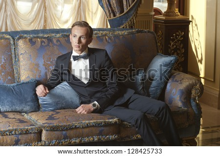 Young blond man in suit and bow tie sitting on blue sofa in old luxury interior
