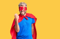 Young blond man wearing super hero custome angry and mad raising fist frustrated and furious while shouting with anger. rage and aggressive concept.