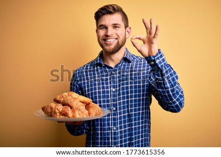 Young blond man with beard and blue eyes holding plate with french croissants to breakfast doing ok sign with fingers, excellent symbol Stock fotó ©