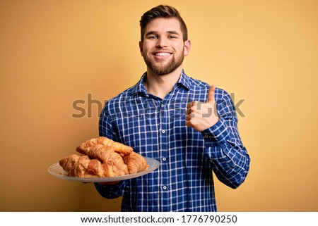 Young blond man with beard and blue eyes holding plate with french croissants to breakfast happy with big smile doing ok sign, thumb up with fingers, excellent sign Stock fotó ©