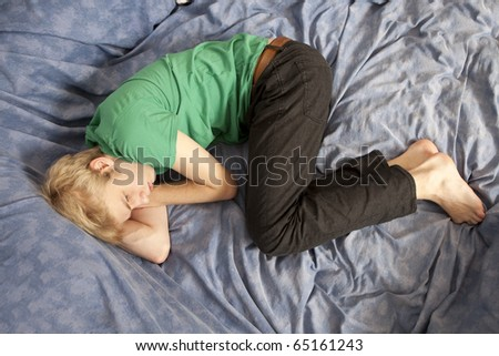 young blond sad man lying on the bed. Teen`s problem. First love.