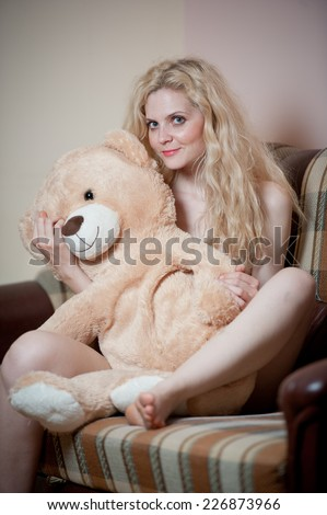 Young blond sensual woman sitting on sofa relaxing with a huge teddy bear. Beautiful girl with comfortable clothes relaxing on the couch with a toy. Attractive blonde in cosy scenery indoor