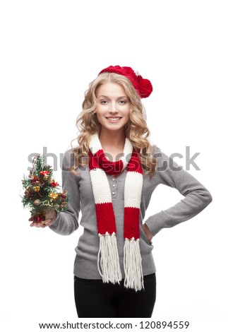 young blond smiling casual woman in red scarf and hat holding christmas tree