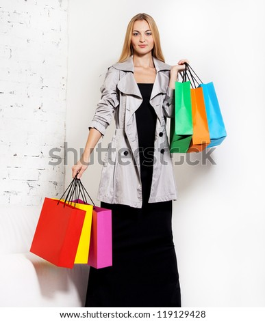 Young blond smiling woman at home after shopping