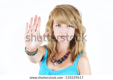 Young blond teenager girl with sad or angry face raising her hand to say NO or STOP, strong concept against drugs, violence, abuse or others: focus on hand in forefront.