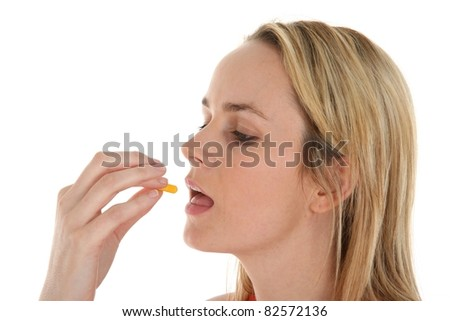 Young blond woman about to insert a yellow medicine capsule into her mouth