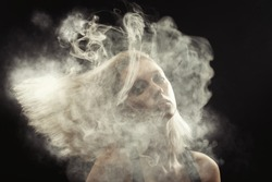 young blond woman dancing at white smoke cloud on black background