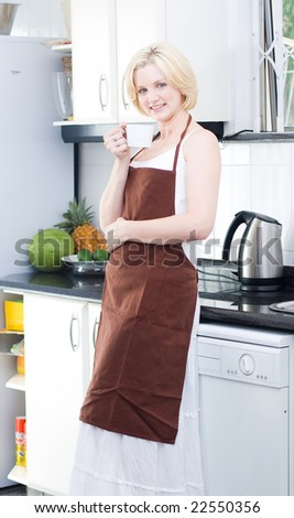 Young blond woman drinking coffee in the kitchen