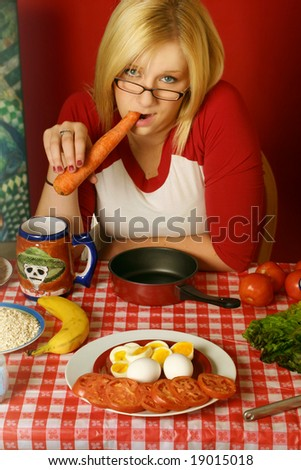 young blond woman eating a carrot and seating at a table