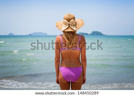 young blond woman enjoying the beach, back