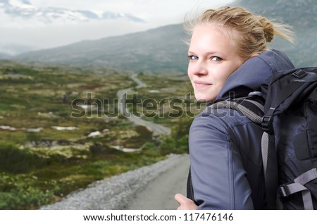 young blond woman hiking with scenery in the background