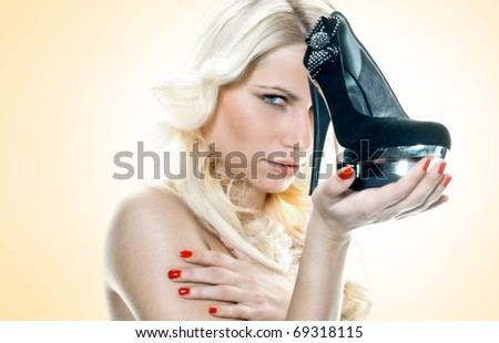 young blond woman holding high heels shoe