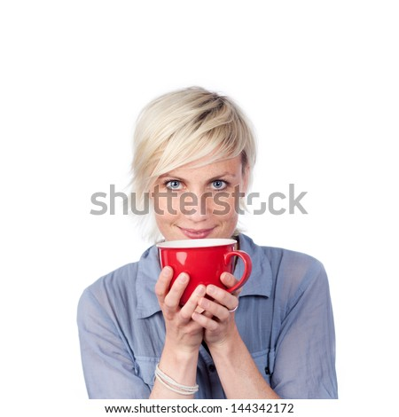 Young blond woman holding red coffee cup against white background