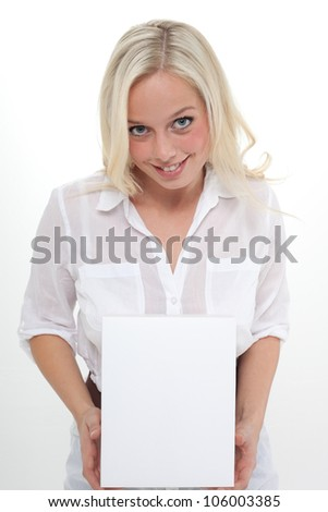 young blond woman holds an empty carton with both hands/young woman with an empty box/woman with a carton
