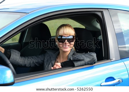 young blond woman in a blue car in sun-glasses. She is smiling