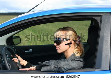 young blond woman in a blue car in sun-glasses with hands free headset