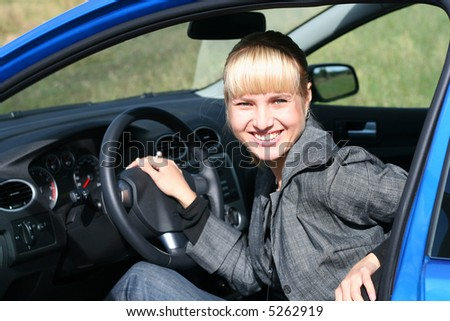 young blond woman in a blue car/ She is smiling happy