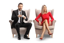 Young blond woman in a red dress  and a man with a cup of coffee sitting in armchairs isolated on white background