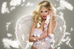 Young blond woman in angel costume with flower