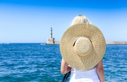 Young blond woman in big hat enjoying the beautiful views of the port of Chania in Venetian style. History Architecture Travel. Chania, Crete Island. Greece.