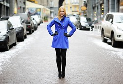 young blond woman in blue coat on modern city street
