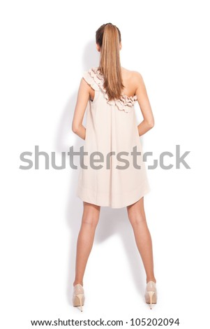 young blond woman in short elegant dress and high heel shoes , back view, full body shot, studio white