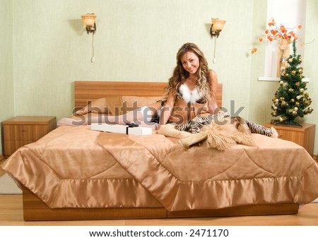 young blond woman in white fur coat and black bikini making a mobile call and a man holding white gift box in his hands, both sitting on the bed in nice interior