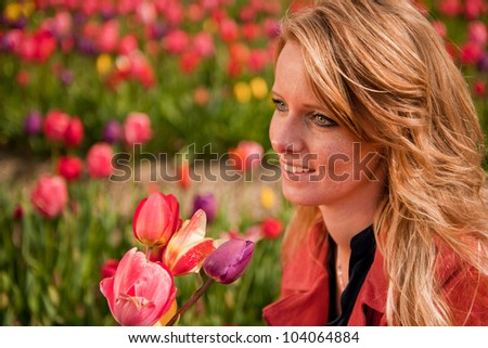 Young blond woman is picking flowers in the Dutch tulips fields