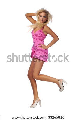 Young blond woman jumping and wearing a pink dress and high heels