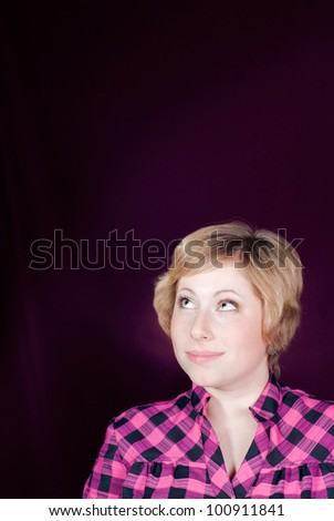 Young blond woman looking up on empty copy space smiling over purple background