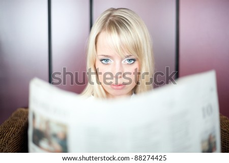 young blond woman looks in a newspaper and is shocked/woman with a newspaper