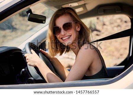 Young blond woman on road trip, smiling