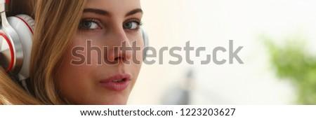 young blond woman portrait lie on sofa listen music dream pleasure concept