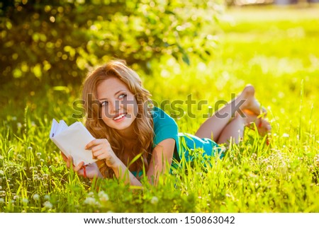young blond woman reading a book lying on the grass in the shade