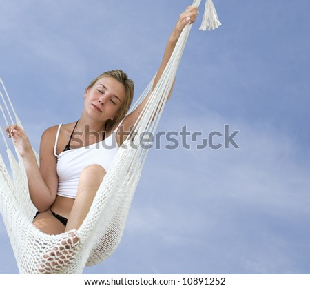 Young blond woman resting in a hammock on a blue sky background