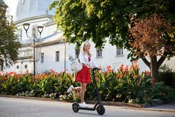 Young blond woman, riding on electric scooter in city center near flowerbeds. Full-length action portrait of female. Summer leisure activity. Spending free time outdoors. Traveler exploring the town.