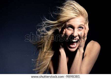 young blond woman screaming in fear, studio