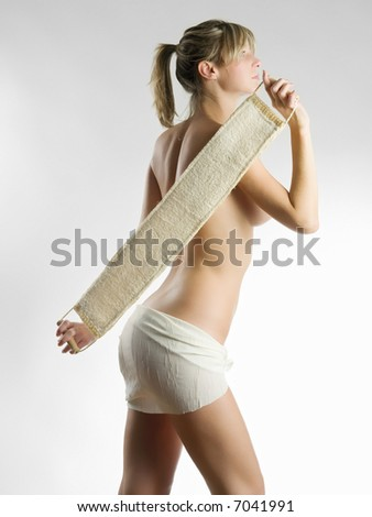 young blond woman scrubbing her shoulder after a shower